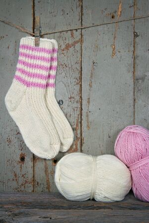 Woolen socks in rustic vintage setting with pink and white yarn - knitting concept photo