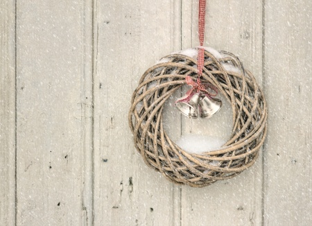 Christmas wreath in snowfall on a vintage wooden background