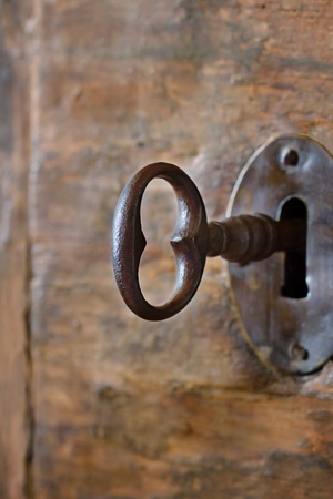antique keys: Closeup of an old keyhole with key on a wooden antique door Stock Photo