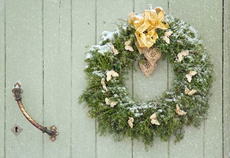 Green Christmas wreath in snowfall on a wooden green rustic door photo