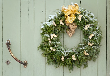 Green Christmas wreath with a golden bow on a wooden green rustic door photo