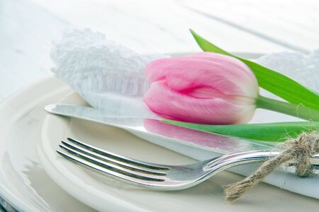 Closeup of pink tulip at rustic dinner setting, on white wooden table photo