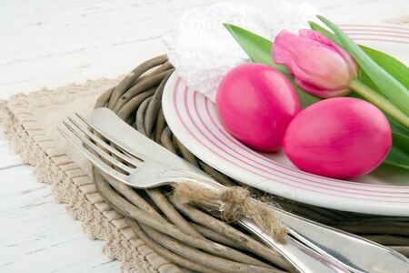 Easter dinner setting with two pink eggs and tulip, rustic white wooden background photo
