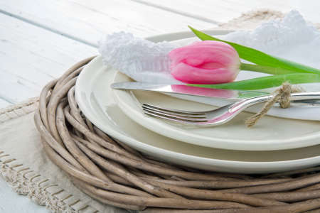Pink tulip on rustic dinner setting on white wooden table photo
