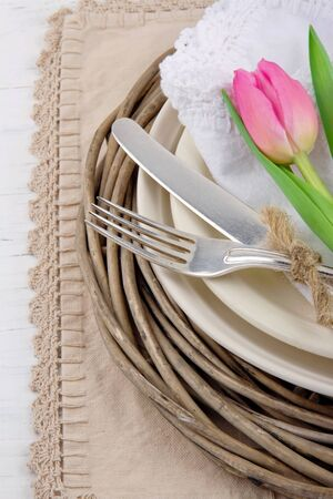 Rustic dinner setting with pink tulip on white wooden table photo