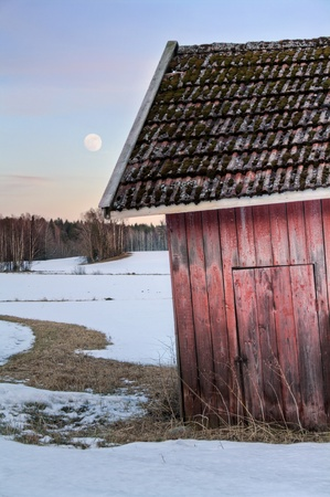 Old red shabby barn in snowy landscape photo