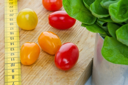 measurement tape: Salad, tomatos and measurement tape - diet and healthy eating; weight loss concept