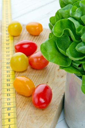 measurement tape: Tomatos, salad and measurement tape - diet and healthy eating; weight loss concept
