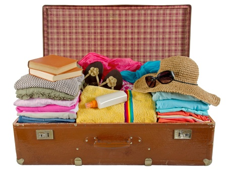 maleta: Old vintage maleta llena de ropa de mujer, sombrero, libros, gafas de sol y toalla de playa