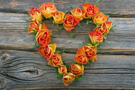 rosas naranjas: Las rosas anaranjadas en forma de coraz�n sobre fondo de madera