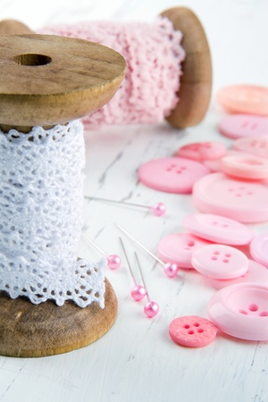 stitchwork: Sewing background with pink buttons and white lace