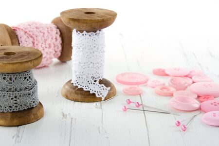 stitchwork: Sewing tools with buttons and lace on white wooden bakcground