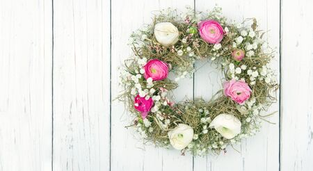 buttercup flower: Pink and white summer flower wreath on white wooden rustic background Stock Photo
