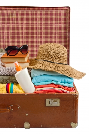Old vintage suitcase packed with sun hat, clothes, books, sunglasses and beach towel photo