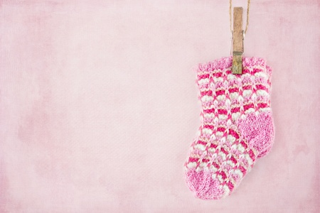 Baby girl woolen socks on textured pastel pink background Stock Photo