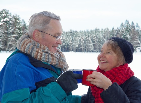 older women: Elderly happy couple toasting with cups of warm drinks, outside in snow winter forest landscape