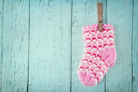 Pink baby socks on a blue wooden rustic background with copy space Stock Photo