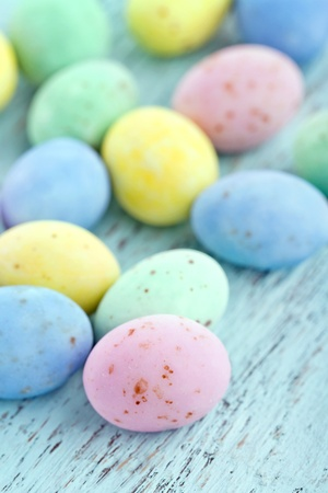 Small chocolate pastel easter eggs on vintage light blue wooden background photo