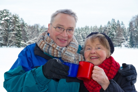 Smiling attractive senior couple outside in snowy winter landscape, holding warm cups of drinks Stock Photo
