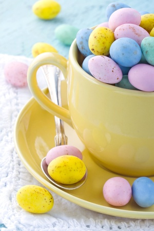 Easter eggs in a yellow cup on wooden vintage background photo