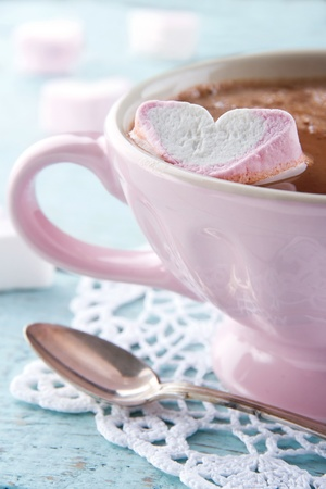 Hot chocolate and a heart shaped marsmallow in a vintage pink cup on light blue wooden background photo