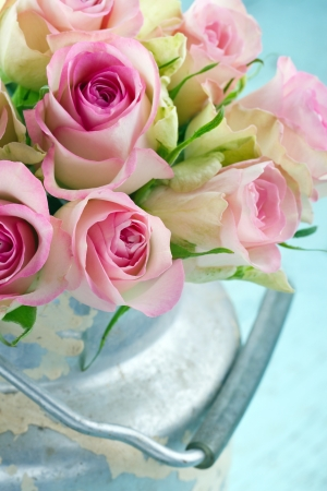 roses in vase: Bouquet of pink romantic roses in a rustic shabby chic bucket Stock Photo