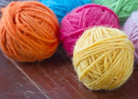 Closeup of colorful woolen yarn on old vintage wooden background