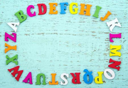 Kolorowe litery alfabetu z miejsca kopiowania, na jasnoniebieskim tle drewniane Zdjęcie Seryjne - 18837603