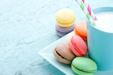 Pastel color macaroons and a cup of milk on vintage light blue wooden background Stock Photo