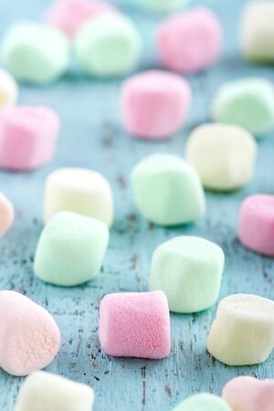 sweet treats: Colorful small marshmallows on light blue wooden background