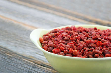 Dried goji berries in a yellow bowl on wooden rustic background, with copy space photo