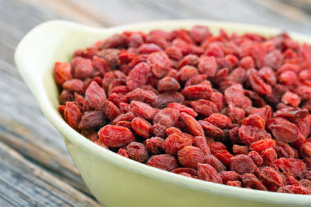 goji berry: Dried goji berries in a yellow bowl on wooden rustic background