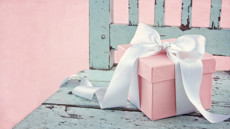Pink romantic gift box with white satin bow on a light blue wooden chair photo
