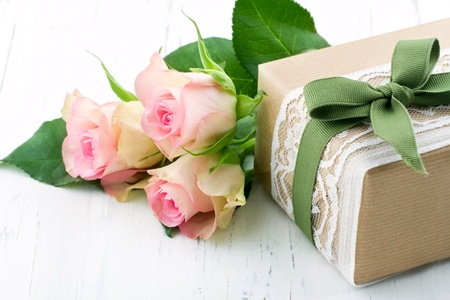 Gift box wrapped in brown paper, white lace and a green bow, with pink roses on wooden vintage background