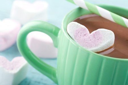 Hot chocolate and a heart shaped marsmallow in a green cup Banco de Imagens