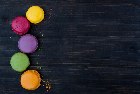 Macaroons background, colorful cookies on black wooden table