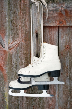 figure skating: Old figure ice skates hanging on a red rustic wooden wall
