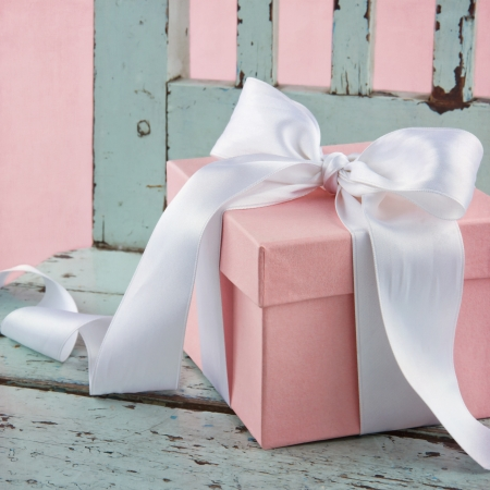 Pink romantic gift box with white satin bow on a light blue wooden chair