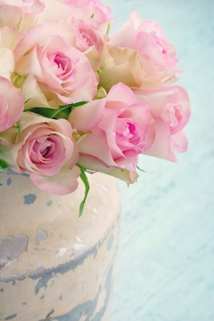 Roses in a shabby chic metal bucket on vintage wooden background