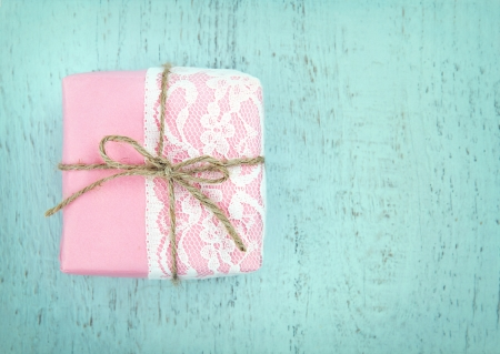 White lace and a simple bow on pink gift box on light blue wooden vintage background - concept for a girl photo