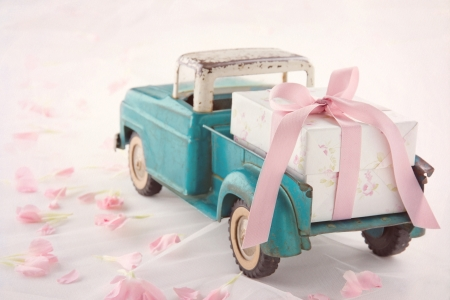 wrapped gift: Old antique toy truck carrying a gift box with pink ribbon on romantic lace background and flower petals Stock Photo