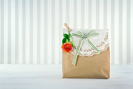 brown paper bags: Brown paper gift bag decorated with doily, orange rose and green striped ribbon