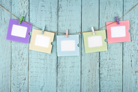 memo: Five empty colorful photo frames or notes paper hanging with clothespins on wooden blue vintage shabby chic background