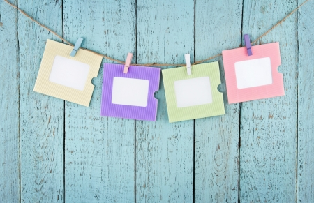 Four empty colorful photo frames or notes paper hanging with clothespins on wooden blue vintage shabby chic background Banco de Imagens
