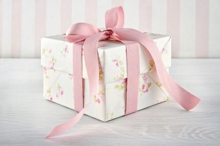 Floral pattern Geschenk-Box mit pink ribbon on white wooden background gebunden Standard-Bild - 19264341