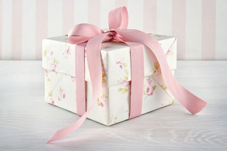 Floral pattern gift box tied with pink ribbon on white wooden background photo