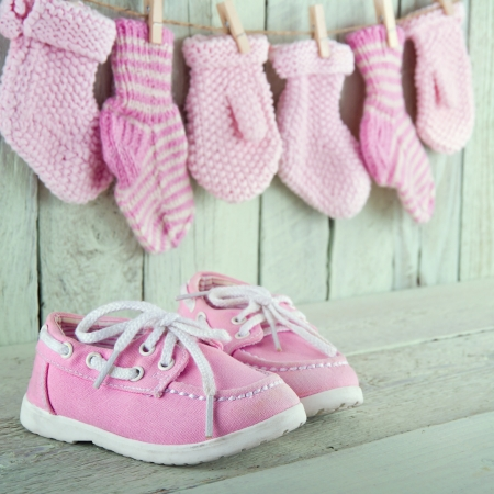 Pink toddler shoes on wooden light green vintage background photo