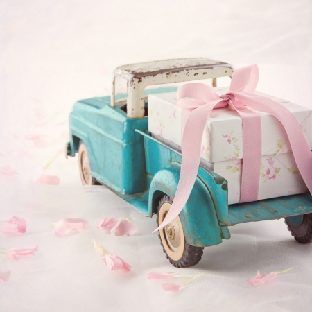 Old antique toy truck carrying a gift box with pink ribbon on romantic lace background and flower petals Stock Photo