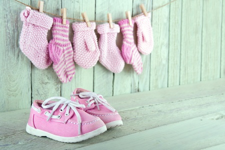 decorative accessories: Pink toddler shoes on wooden light green vintage background Stock Photo