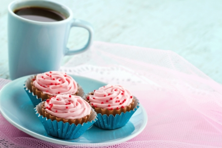 Blue plate with pink chocolate pralines and cup of coffee on pastel color background, with copy space photo